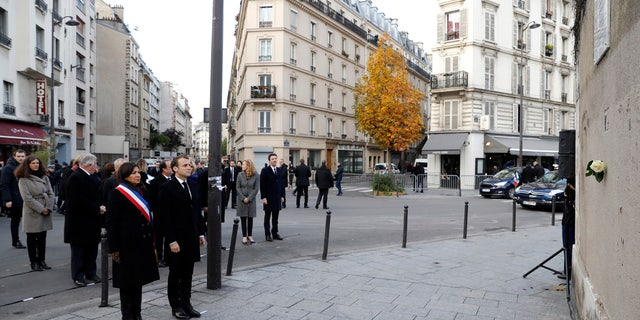 French President Emmanuel Macron and Paris mayor Anne Hidalgo, left, stand in front of a commemorative plaque facing the 'Le Carillon' bar and 'Le Petit Cambodge' restaurant during a ceremony marking the second anniversary of the Paris attacks, Monday Nov.13 November 2017.
