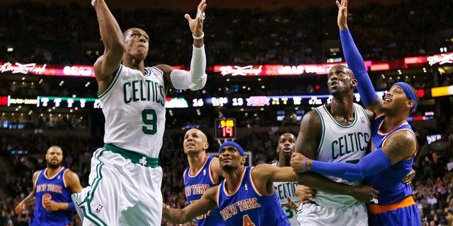Boston Celtics guard Rajon Rondo (9) drives to the basket as Kevin Garnett blocks out New York Knicks forward Carmelo Anthony, right, during the first quarter of an NBA basketball game in Boston, Thursday, Jan. 24, 2013. (AP Photo/Charles Krupa)