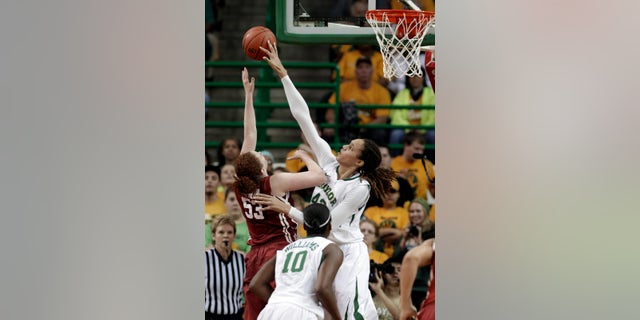 FILE - In this Jan. 26, 2013 file photo, Baylor's Brittney Griner (42) blocks the shot of Oklahoma's Joanna McFarland (53) during the second half of an NCAA college basketball game in Waco Texas. Griner was selected to the 2012-13 AP Women'sAll-America team, Tuesday, April 2, 2013.  (AP Photo/LM Otero, FIle)