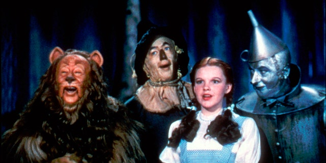 """Bert Lahr as the Cowardly Lion, Ray Bolger as the Scarecrow, Judy Garland as Dorothy and Jack Haley as the Tin Woodman in a scene from """"The Wizard of Oz."""""""