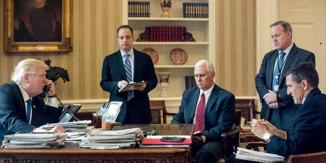 FILE - In this Jan. 28, 2017 file photo, President Donald Trump accompanied by, from second from left, Chief of Staff Reince Priebus, Vice President Mike Pence, White House press secretary Sean Spicer and then-National Security Adviser Michael Flynn speaks on the phone with Russian President Vladimir Putin, in the Oval Office at the White House in Washington.