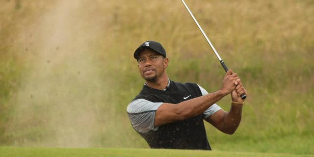 Tiger Woods of the US plays a shot from the bunker near the 15th green during a practice round at Royal Liverpool Golf Club prior to the start of the British Open Golf Championship, in Hoylake, England, Saturday, July 12, 2014. The 2014 Open Championship starts on Thursday July 17. (AP Photo/Jon Super)