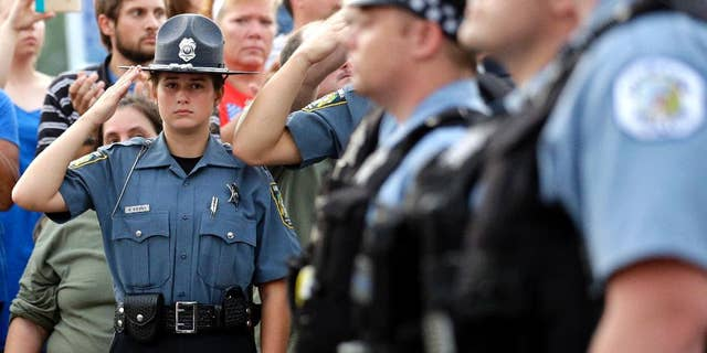 A police explorer salutes as police officials follow Fox Lake Police Lt. Charles Joseph Gliniewicz's family after a vigil at Lakefront Park.