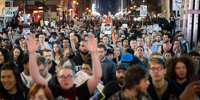 Protestors march up Seventh Avenue towards Times Square after the announcement of the grand jury decision not to indict police officer Darren Wilson in the fatal shooting of Michael Brown, an unarmed 18-year-old black man, Monday, Nov. 24, 2014, in New York. (AP Photo/John Minchillo)