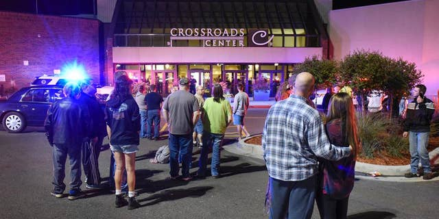 FILE - In this Sept. 17, 2016, file photo, people stand near an entrance of Crossroads Center shopping mall in St. Cloud, Minn., after several people were stabbed. FBI Director James Comey said Wednesday, Sept. 28, 2016, that the man who stabbed multiple people in the mall before being shot and killed appears to have been inspired, at least in part, by extremist ideology. (Dave Schwarz/St. Cloud Times via AP File)