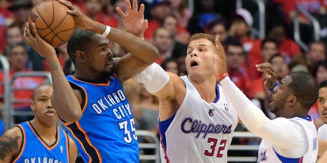 Oklahoma City Thunder forward Kevin Durant, left, passes the ball as Los Angeles Clippers forward Blake Griffin, center, and guard Chris Paul defend in the first half of Game 3 of the Western Conference semifinal NBA basketball playoff series, Friday, May 9, 2014, in Los Angeles. (AP Photo/Mark J. Terrill)