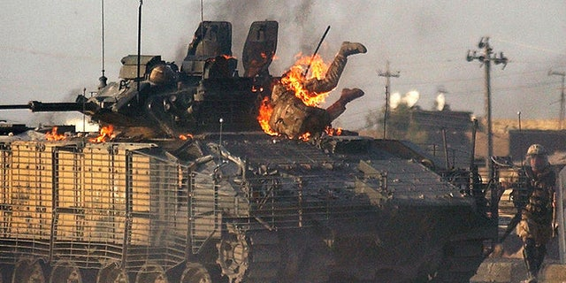A British soldier makes his way out of a burning Warrior fighting vehicle in Basra, 550 kilometers (340 miles) southeast of Baghdad Monday Sept. 19, 2005.
