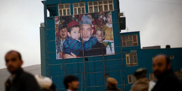 Afghan men waiting to get a ride out of the city line up next to a giant poster of Afghanistan's President Hamid Karzai in Kabul, in 2009.