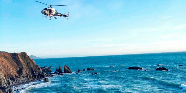 A helicopter hovers over steep coastal cliffs near Mendocino, Calif., where a vehicle plunged about 100 feet off a cliff.