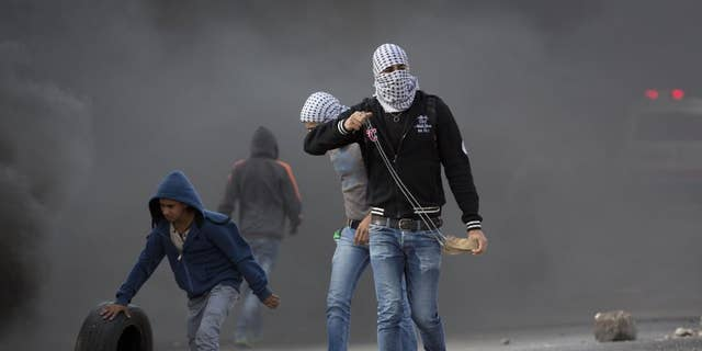 Palestinian protesters prepare to throw stones at Israeli troops Tuesday.