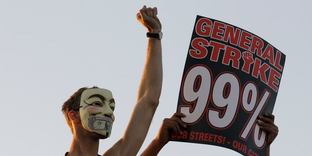 """FILE — In this Nov. 2, 2011 photo, Occupy Wall Street protestors stand on top of a parked semi truck during a march from downtown Oakland, Calif., to the port of Oakland. From New York to San Francisco to London, some of the demonstrators decrying a variety of society's ills are sporting stylized masks loosely modeled on a 17th-century English terrorist, whether they know it or not. The masks come from """"V for Vendetta,"""" a comic-based movie whose violent, anarchist antihero fashions himself as a modern Guy Fawkes, the Catholic insurrectionist executed four centuries ago for trying to blow up Parliament. (AP Photo/Jeff Chiu)"""