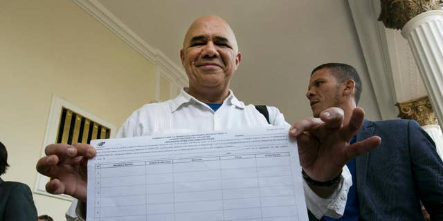 Jose Torrealba executive secretary of Venezuela's opposition coalition, Mesa de la Unidad Democratica, MUD, shows one of the petition sheets needed to collect around 200,000 signatures to allow MUD to try and initiate a recall referendum against President Nicolas Maduro, at the National Assembly building in Caracas, Venezuela, Tuesday, April 26, 2016. Although Maduro's approval rating has plummeted amid spiraling triple-digit inflation, a deep recession and widespread shortages, booting him from office won't be easy. (AP Photo/Ariana Cubillos)