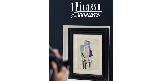 """December 12, 2013: Pablo Picasso's 1914 painting """"Man with Opera Hat"""" on display in Paris (AP Photo)"""