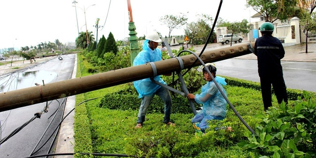 Workers repair a fallen electricity pole in the central province of Phu Yen, Vietnam, Saturday, Nov. 4, 2017.