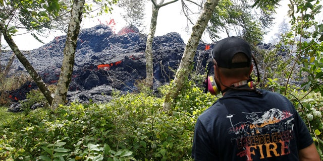 An onlooker watches as lava erupts from a fissure east of the Leilani Estates subdivision during ongoing eruptions of the Kilauea Volcano