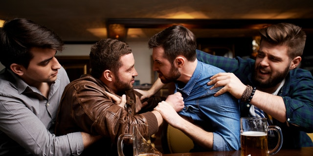 Drunk men fighting in pub, their friends trying to pull them apart, broken beer mug on bar counter