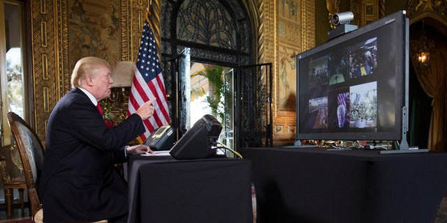 President Donald Trump communicates with U.S. troops via a video hook-up at his home in Palm Beach, Fla., Dec. 24, 2017.
