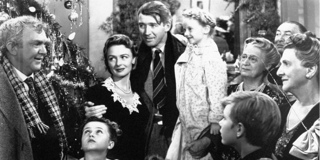 """FILE -  In this 1946 file photo originally provided by RKO Pictures Inc., legendary actor James Stewart as George Bailey, center, is reunited with his wife played by actress Donna Reed, third from left, and family during the last scene of Frank Capra's """"It's A Wonderful Life.""""  (AP Photo/RKO Pictures Inc.)"""