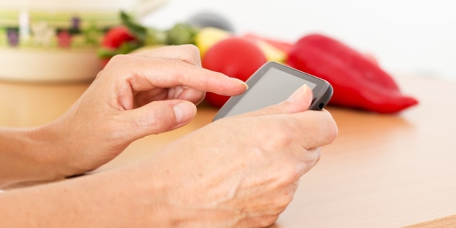 Woman reading a recipe on her smart phon.