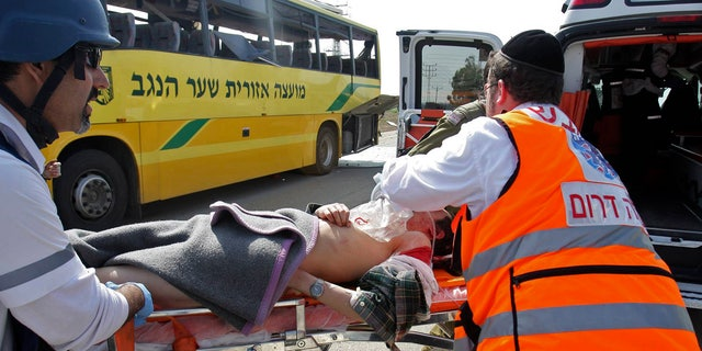 April 7: A wounded Israeli is treated by medics at the site where an Israeli school bus was hit by a mortar shell fired from the Gaza Strip near the border between southern Israel and Gaza Wednesday. A Palestinian mortar shell from the Gaza Strip struck a school bus in southern Israel Thursday, wounding two people, including one child critically, Israeli officials said.