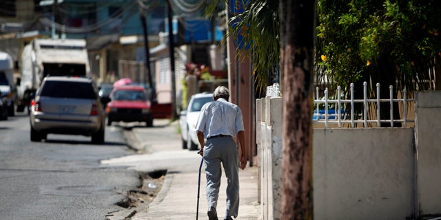 In this Nov. 14, 2013 photo, Mariano Perez Morales, 75, walks a sidewalk in Barceloneta, Puerto Rico.