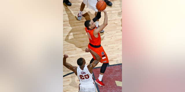 Syracuse guard Tyler Ennis (11), who had 16 points, shoots by Florida State guard Aaron Thomas (25) in the first half of an NCAA college basketball game Sunday, March 9, 2014, at the Donald L. Tucker Center in Tallahassee, Fla. Syracuse defeated Florida State 74-58. (AP Photo/Phil Sears)