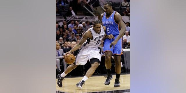 San Antonio Spurs' Kawhi Leonard (2) drives around Oklahoma City Thunder's Kendrick Perkins (5) during the first half of an NBA basketball game, Wednesday, Jan. 22, 2014, in San Antonio. The Thunder won 111-105. (AP Photo/Eric Gay)