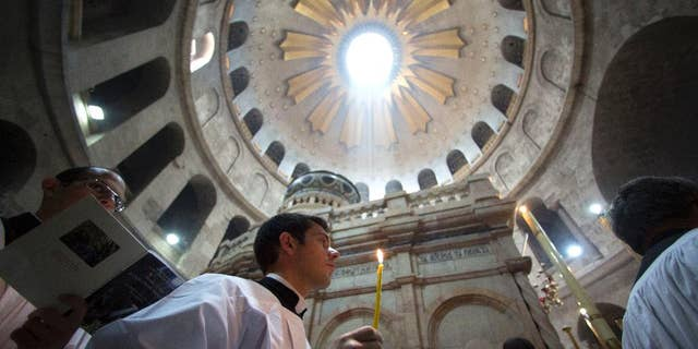 Christian pilgrims light candles during the Easter Sunday procession at the Church of the Holy Sepulchre, traditionally believed by many Christians to be the site of the crucifixion and burial of Jesus Christ, in Jerusalem, Sunday, April 16, 2017. (AP Photo/Sebastian Scheiner)