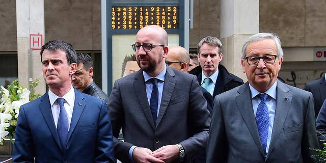 From left, French Prime Minister Manuel Valls, Belgian Prime Minister Charles Michel and European Commission President Jean-Claude Juncker prepare to lay flowers at the Maelbeek metro station in Brussels on Wednesday, March 23, 2016. Belgian authorities were searching Wednesday for a top suspect in the country's deadliest attacks in decades, as the European Union's capital awoke under guard and with limited public transport after scores were killed and injured in bombings on the Brussels airport and a subway station. (Emmanuel Dunand, Pool Photo via AP)