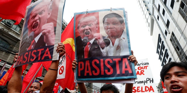 """Protesters shout slogans holding portraits of U.S. President Donald Trump and Philippines President Rodrigo Duterte during a rally near the U.S. Embassy in Manila, Nov. 10, 2017. The sign translates to """"Fascist."""""""