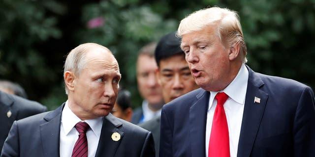 U.S. President Donald Trump and Russia's President Vladimir Putin talk during the family photo session at the APEC Summit in Danang, Vietnam November 11, 2017. REUTERS/Jorge Silva - RC1B1EDB0E40