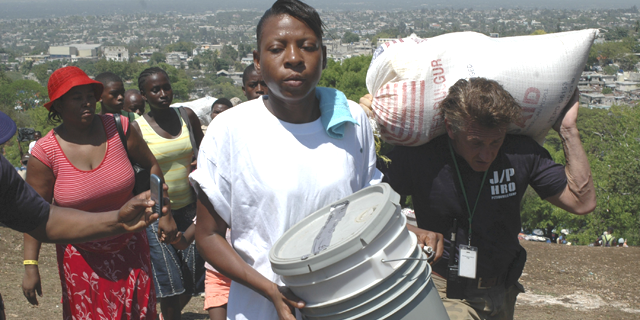 Sean Penn (R) helps to carry the belongings of a earthquake victims during a relocation exercise in Port-au-Prince April 10, 2010. (Reuters)