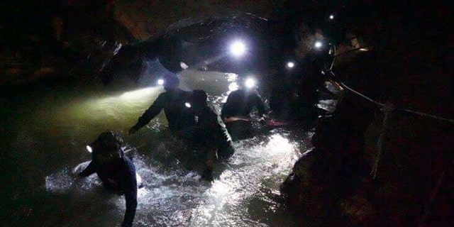 In this handout photo released by Tham Luang Rescue Operation Center, Thai rescue teams walk inside a cave complex where 12  in Mae Sai, Chiang Rai province, in northern Thailand, Monday, July 2, 2018.