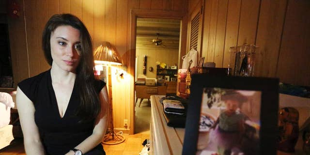 "In this Feb. 13, 2017 photo, Casey Anthony poses for a portrait next to a photo of her daughter, Caylee, in her West Palm Beach, Fla., bedroom. In an exclusive interview with The Associated Press, Anthony claims the last time she saw Caylee she ""believed that she was alive and that she was going to be OK."" (AP Photo/Joshua Replogle)"