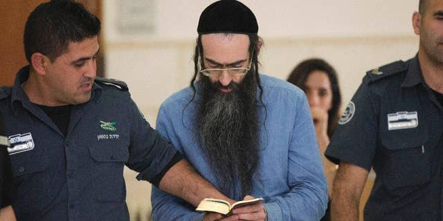 Yishai Schlissel, who fatally stabbed a teenage girl and wounded others at last year Jerusalem's gay pride parade, reads scripture at court in Jerusalem, Tuesday, April 19, 2016. The District Court convicted Schlissel for murder for last year's deadly attack, along with multiple attempted murder charges for those he wounded. (AP Photo/Oded Balilty)