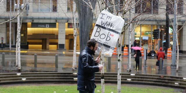 """A person walks outside the federal courthouse in Seattle carrying a sign that reads """"I'm with Bob and Immigrants,"""" in reference to Washington state Attorney General Bob Ferguson, Friday, Feb. 3, 2017, during a hearing in federal court. A U.S. judge on Friday temporarily blocked President Donald Trump's ban on people from seven predominantly Muslim countries from entering the United States after Washington state and Minnesota urged a nationwide hold on the executive order that has launched legal battles across the country. (AP Photo/Ted S. Warren)"""