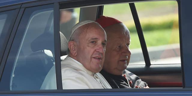 In this July 31, 2016 file photo pope Francis and Krakow cardinal Stanislaw Dziwisz, right, are arriving in a navy blue Volkswagen Golf car to celebrate a Holy Mass there. The car, along with two other similar VW Golf care that Francis was driven in in Poland has been put on auction by a Polish Catholic Church charity to raise funds for a mobile clinic for Syrian refugees in Lebanon and for a shelter for the disabled in Poland. (AP Photo/Alik Keplicz, file)