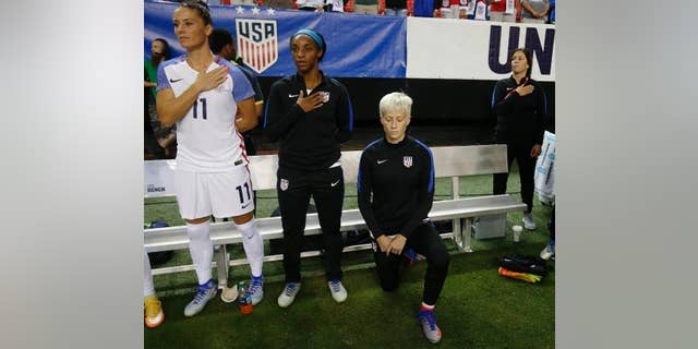 FILE - In this Sunday, Sept. 18, 2016 file photo, United States' Megan Rapinoe, right, kneels next to teammates Ali Krieger (11) and Crystal Dunn (16) as the U.S. national anthem is played before an exhibition soccer match against Netherlands in Atlanta. (AP Photo/John Bazemore, File)