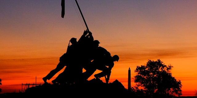 The rising sun turns the sky red and orange behind the U.S. Marine Corps War Memorial Friday, Nov. 3, 2017, in Arlington, Va. (AP Photo/J. David Ake)