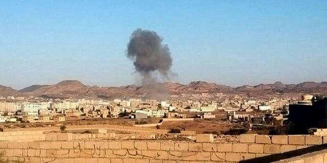 Smoke rises from the site of a car bomb explosion in Radda town,100 miles (160 kilometers) south of the capital Sanaa, Yemen, Tuesday, Dec. 16, 2014. Two suicide car bombers rammed their vehicles into a Shiite rebels' checkpoint and a house south of the Yemeni capital Tuesday, as a school bus traveling nearby killing at least 25 dead including at least 15 primary school students, Defense Ministry, rebels and witnesses. (AP Photo)