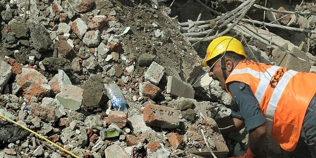 An Indian National Disaster Relief Force worker shouts as he looks for survivors in the debris at a building collapse site in Mumbai on September 28, 2013