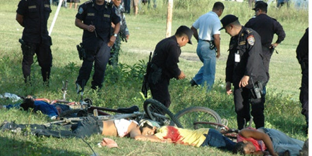 Police officers inspect the bodies of victims of a massacre in a soccer field in San Pedro Sula,  Honduras, Saturday Oct. 30, 2010.  A carful of attackers armed with assault rifles drove up to the football field  Saturday and opened fire, killing at least 14 people.(AP Photo)