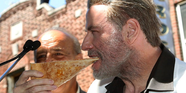 "John Travolta, star of ""Gotti,"" eats a slice of pizza in Brooklyn, N.Y., to commemorate his 1970s role in ""Saturday Night Fever,"" June 12, 2018."