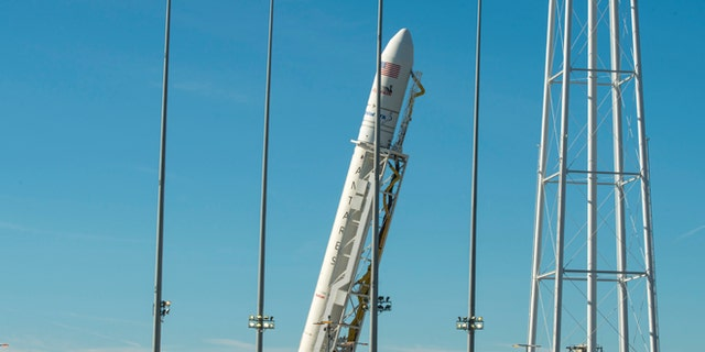 In this photo released by NASA, the Orbital ATK Antares rocket, with the Cygnus spacecraft onboard, is raised into the vertical position on launch Pad-0A, Friday, Oct. 14, 2016, at NASA's Wallops Flight Facility in Virginia.