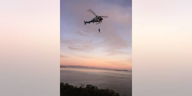 ADDS DAY AND DATE - In this photo provided by the National Park Service a California Highway Patrol helicopter lifts a suspect to safety during the rescue of two suspected vandals at Golden Gate National Recreation Area Thursday Feb. 26, 2015. Park service spokeswoman Alexandra Picavet says the men got stuck on a cliff at the waterfront of Fort Baker in Golden Gate National Recreation Area.  She says they saw rangers approaching and tried to evade arrest by scrambling down a cliff near the water's edge. (AP Photo/U.S. National Park Service)