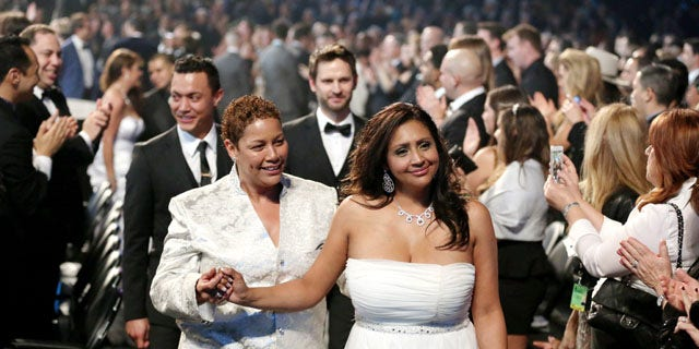 """January 26, 2014: Audience members participate in a same sex wedding during a performance of """"Same Love"""" by Macklemore and Ryan Lewis at the 56th annual Grammy Awards at Staples Center in Los Angeles. With Queen Latifah presiding from the stage and the music playing, 33 straight and gay couples lined the aisle dressed in wedding finery. Under Latifah's command, they exchanged rings near the end of Sunday night's show televised on CBS. (Photo by Matt Sayles/Invision/AP)"""