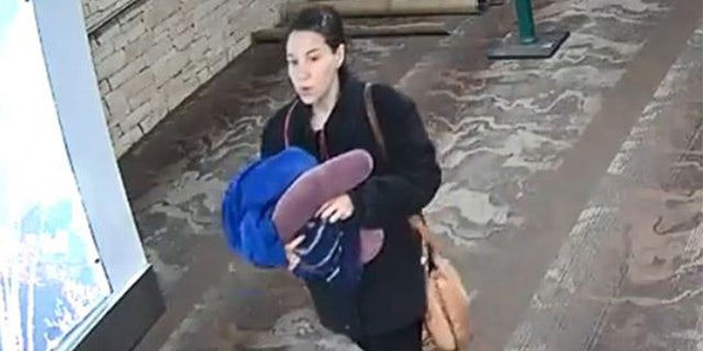 Authorities believe the woman who left the baby to be in her 20s between 5 foot 5 inches and 5 foot 7 inches. In this surveillance footage she is seen carrying a covered bundle toward the bathroom.