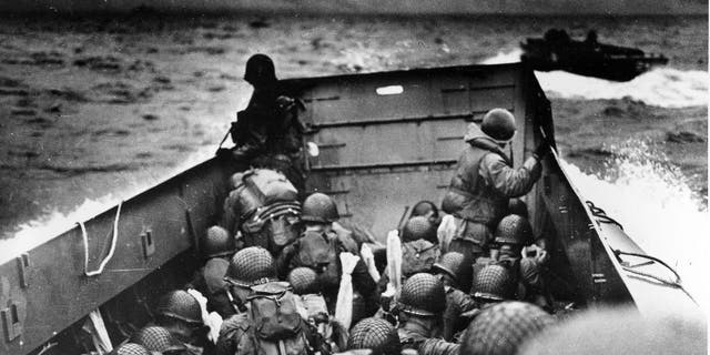 "FILE - In this June 6, 2014 file photo, allied troops crouch behind the bulwarks of a landing craft as it nears Omaha Beach during a landing in Normandy, France. The D-Day invasion broke through Adolf Hitler's western defenses and led to the liberation of France from Nazi occupation just as the Soviet Army was making advances in the east, turning the tide of the war in the Allies' favor.  Allied troops landed on the Normandy coast of France in tremendous strength by cloudy daylight today and stormed several miles inland with tanks and infantry in the grand assault which Gen. Dwight D. Eisenhower called a crusade in which ""we will accept nothing less than full victory.""(AP Photo/U.S. Coast Guard, File)"