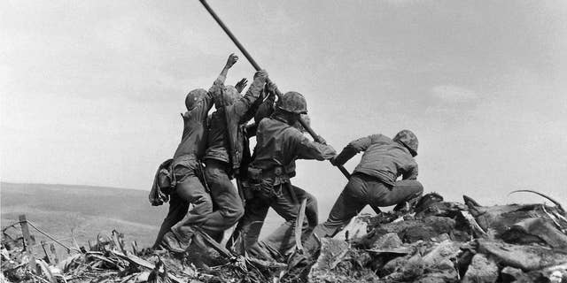 FILE - In this Feb. 23, 1945 file photo, U.S. Marines of the 28th Regiment, 5th Division, raise a U.S. flag atop Mount Suribachi, Iwo Jima. Strategically located 660 miles from Tokyo, the Pacific island became the site of one of the bloodiest, most famous battles of World War II against Japan. (AP Photo/Joe Rosenthal, File)