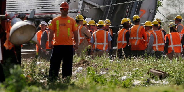 Emergency personnel gather near the scene of a deadly train derailment, Wednesday, May 13, 2015, in Philadelphia.
